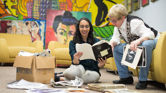 Picture of Facutly sorting books with student
