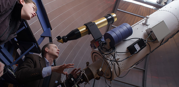 Picture of student and professor looking at a telescope