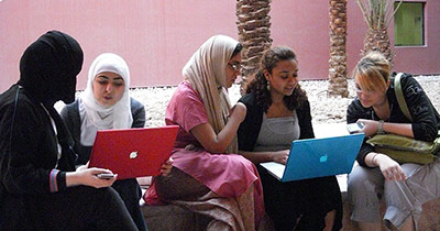 Group of Qatar students looking at laptops