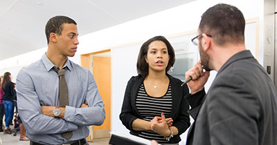 Female student in conversation with two male students
