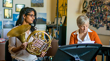 Picture of a student with her french horn working with a professor