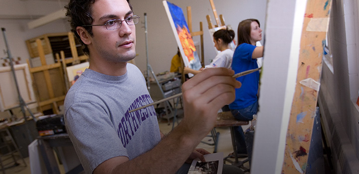 Picture of Northwestern student painting on a canvas