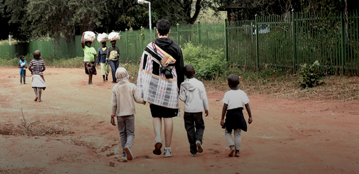 Student walking with children while studying abroad