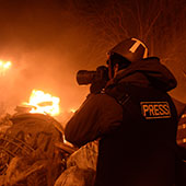 Photographer working at night amidst explosions and fire