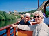 Jean Woolverton Yale, left, and Gwyn Davies Rahr (SESP57) cruise on the Dordogne River toward Beynac Castle.
