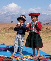 Peruvian children sell souvenirs on the roadside.