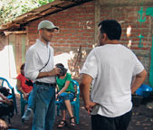 Peace Corps administrator Bryan Dwyer talks with a doctor, who is part of a medical brigade, in a small Salvadoran village with no medical services of its own.